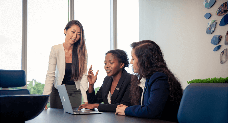 Image depicting 3 business women discussing corporate things in front of a Macbook