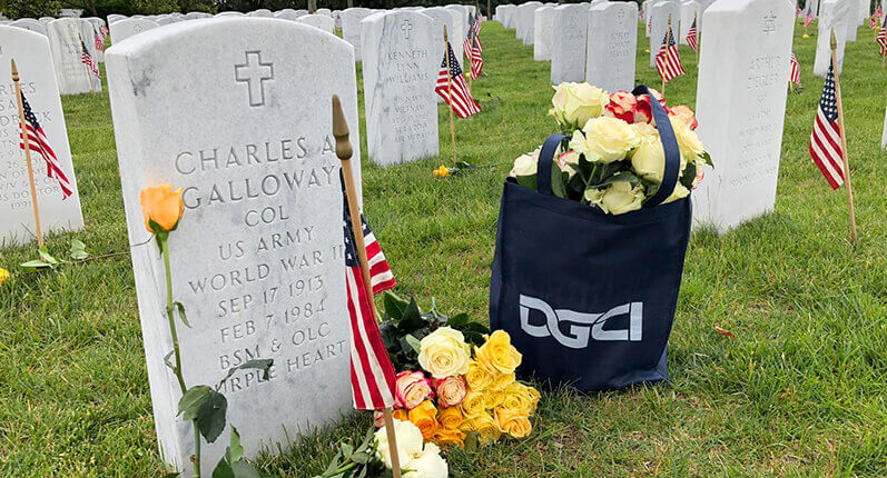 Image depicting bags flowers from DGCI standing beside a Tomb Stone of WW2 soldier